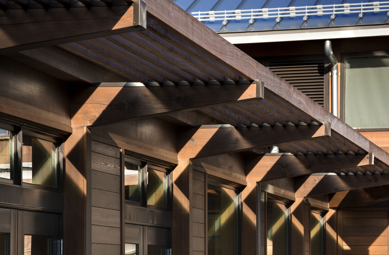 <p>The cloister-like, single-loaded corridor design includes deep exterior eaves and south-facing sunshades that minimize summer solar heat gain but allow beneficial winter heat gain.</p>
